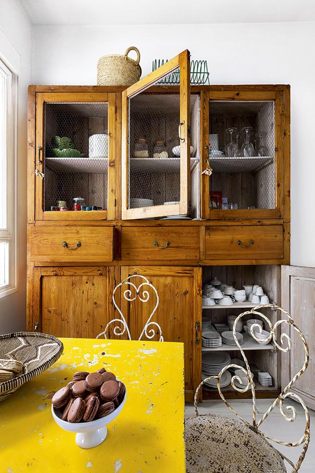 Na cozinha, a cristaleira de Pinho comprada na Europa é combinada com uma mesa de metal comprada em Madrid e cadeiras de jardim francesas do século XIX