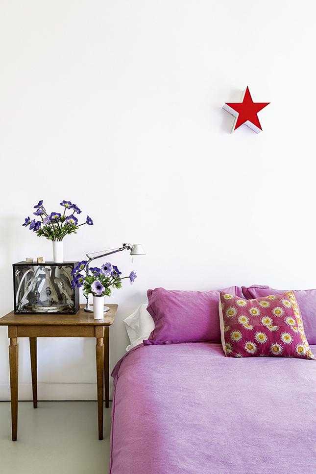 Na cama, edredon Ikea e almofada da Anthropologie.  Mesa de cabeceira comprada em Paris com abajur caixa de luz e ossário de Carlos Bustamante. Na parede, estrela de metalacrilato.