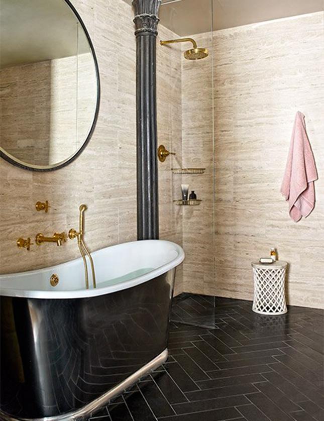O banheiro master tem paredes em mármore travertino, metais dourados e banheira retrô. O conjunto cria um visual clássico e muito chic!