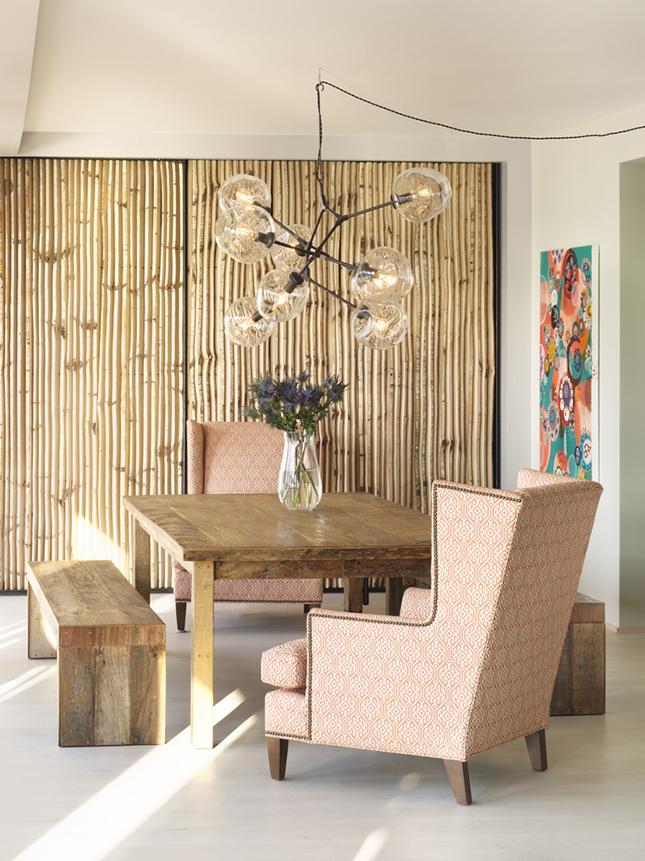 Essa sala ganha um toque mais romântico com o conjunto que mistura madeira natural e poltronas com espaldar alto revestidas em tecido rosé.